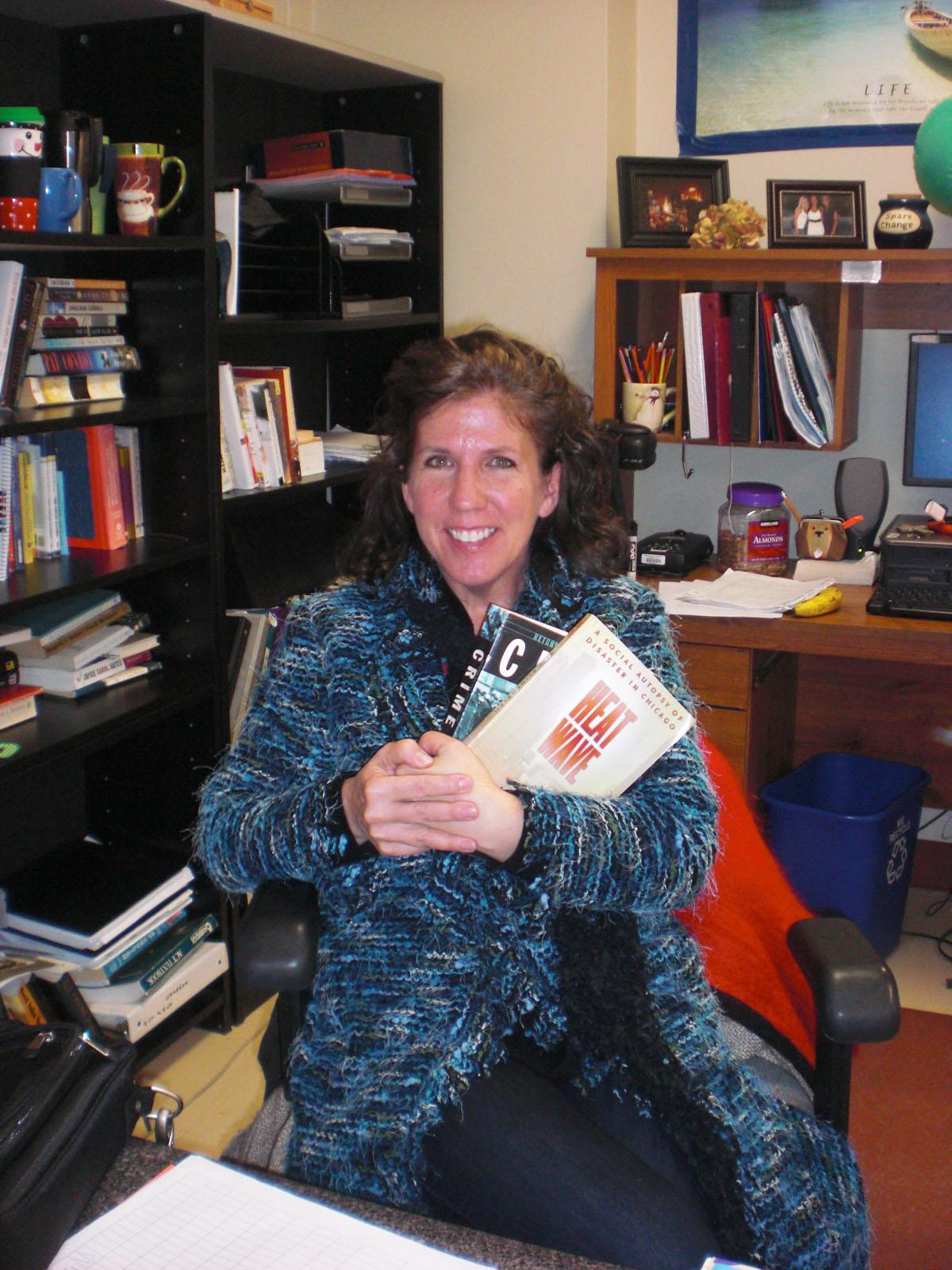 Kathy Meyer holds textbooks for next year's new classes (M. Wilson).