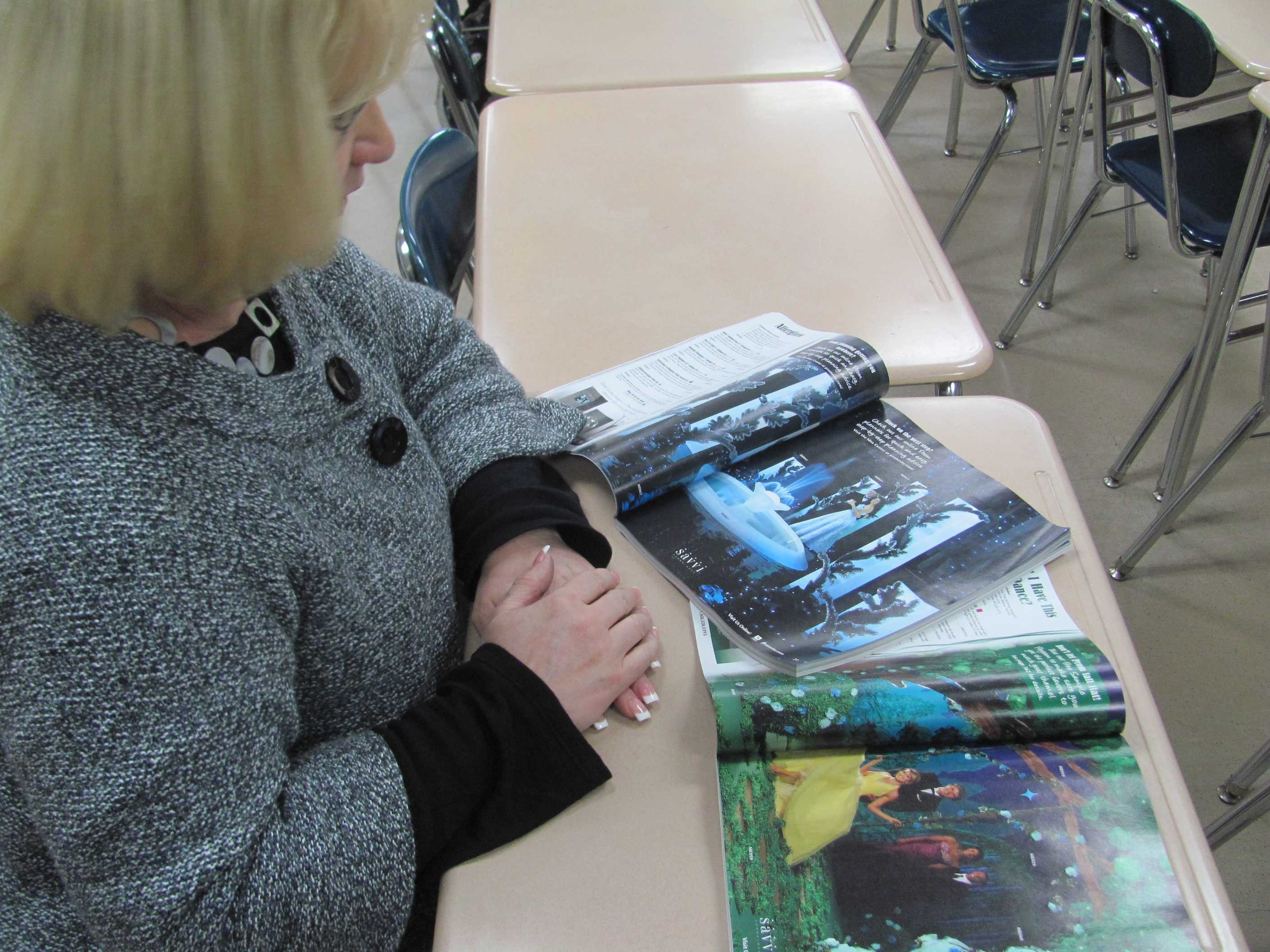 Cindy Fuhrer, Student Council teacher representative looks on at Prom magazines. (Omo Tseumah,Voice)