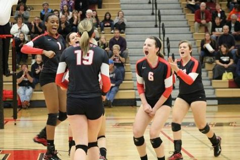 Volleyball players Sydney Holt, Kelsey DeWulf, Ally Dion, and Lexi Smith celebrate a kill made by Erin Erb during the regional game against Jacobs.