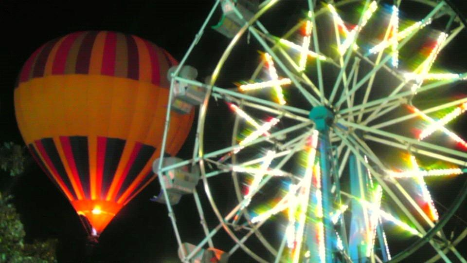 Ferris wheel passengers have a great view of the hot air balloon tether ride late Saturday night. (9/26)