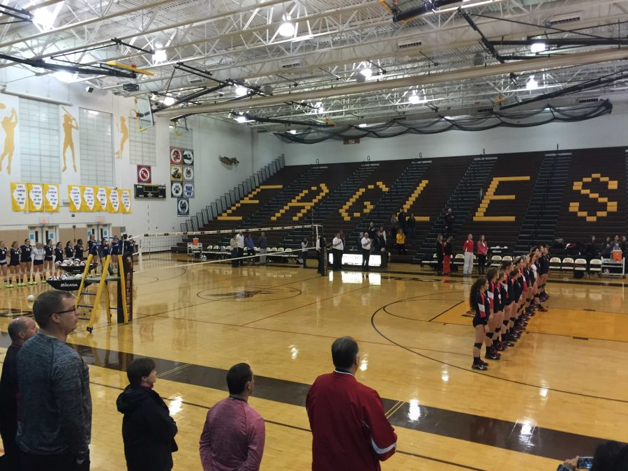 The+Huntley+Red+Raiders+varsity+volleyball+team+stands+for+the+national+anthem+before+their+regional+championship.