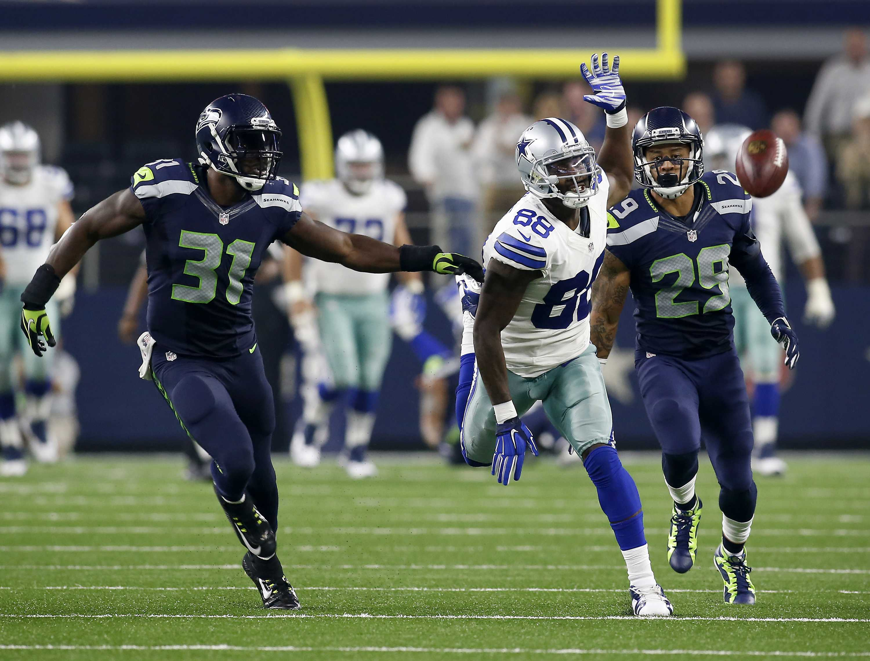 Dallas Cowboys wide receiver Dez Bryant (88) can't reach a deep ball as Seattle Seahawks strong safety Kam Chancellor (31) and Seattle Seahawks' Earl Thomas (29) defend late in the second half on Sunday, Nov. 1, 2015, at AT&T Stadium in Arlington, Texas. (Brad Loper/Fort Worth Star-Telegram/TNS)