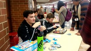 Senior Christian Olivera sells two packages of fruit snacks for a dollar.