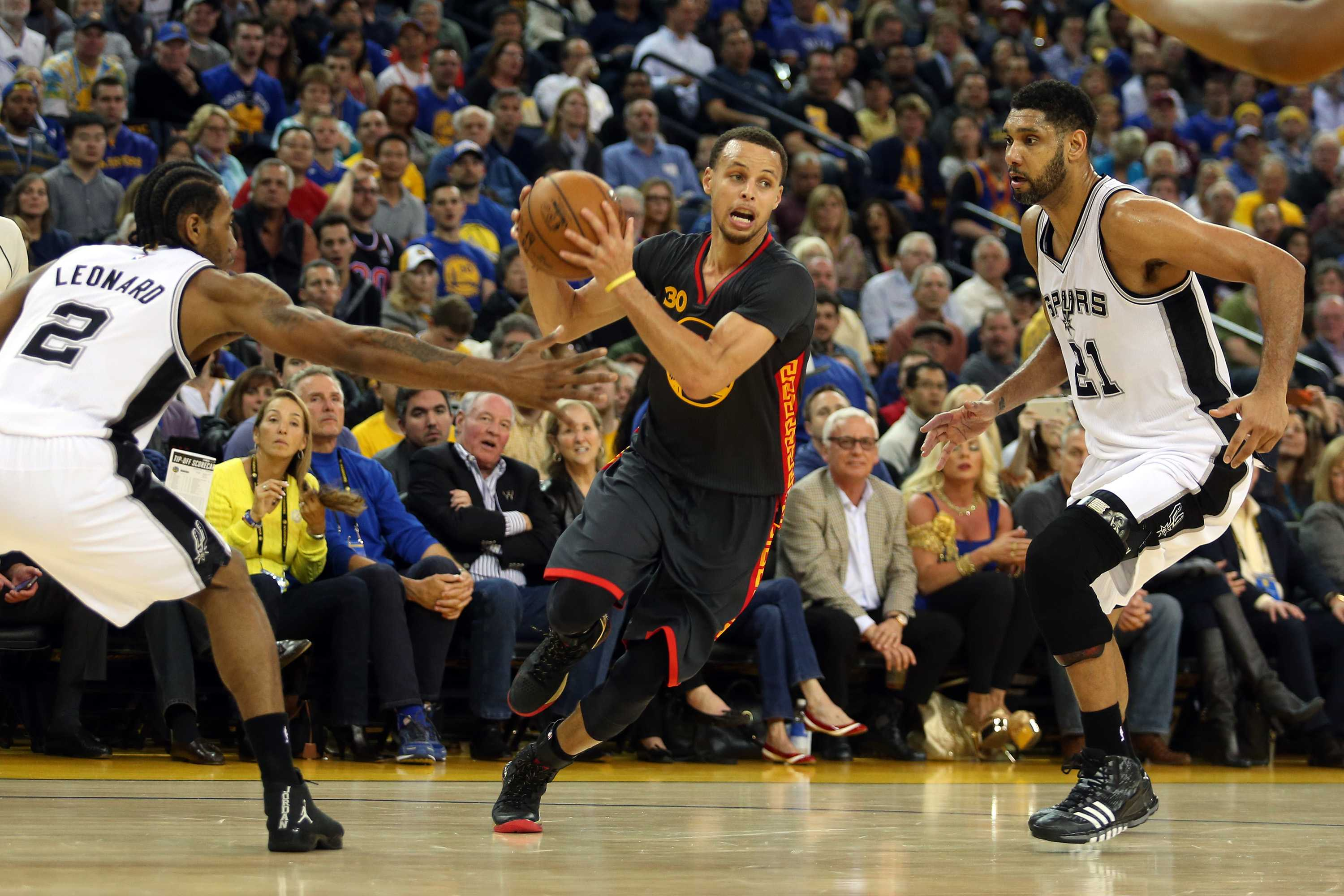 The Golden State Warriors' Stephen Curry (30) drives past the San Antonio Spurs' Kawhi Leonard (2) and Tim Duncan (21) in the first half at Oracle Arena in Oakland, Calif., on Friday, Feb. 20, 2015. (Ray Chavez/Bay Area News Group/TNS)