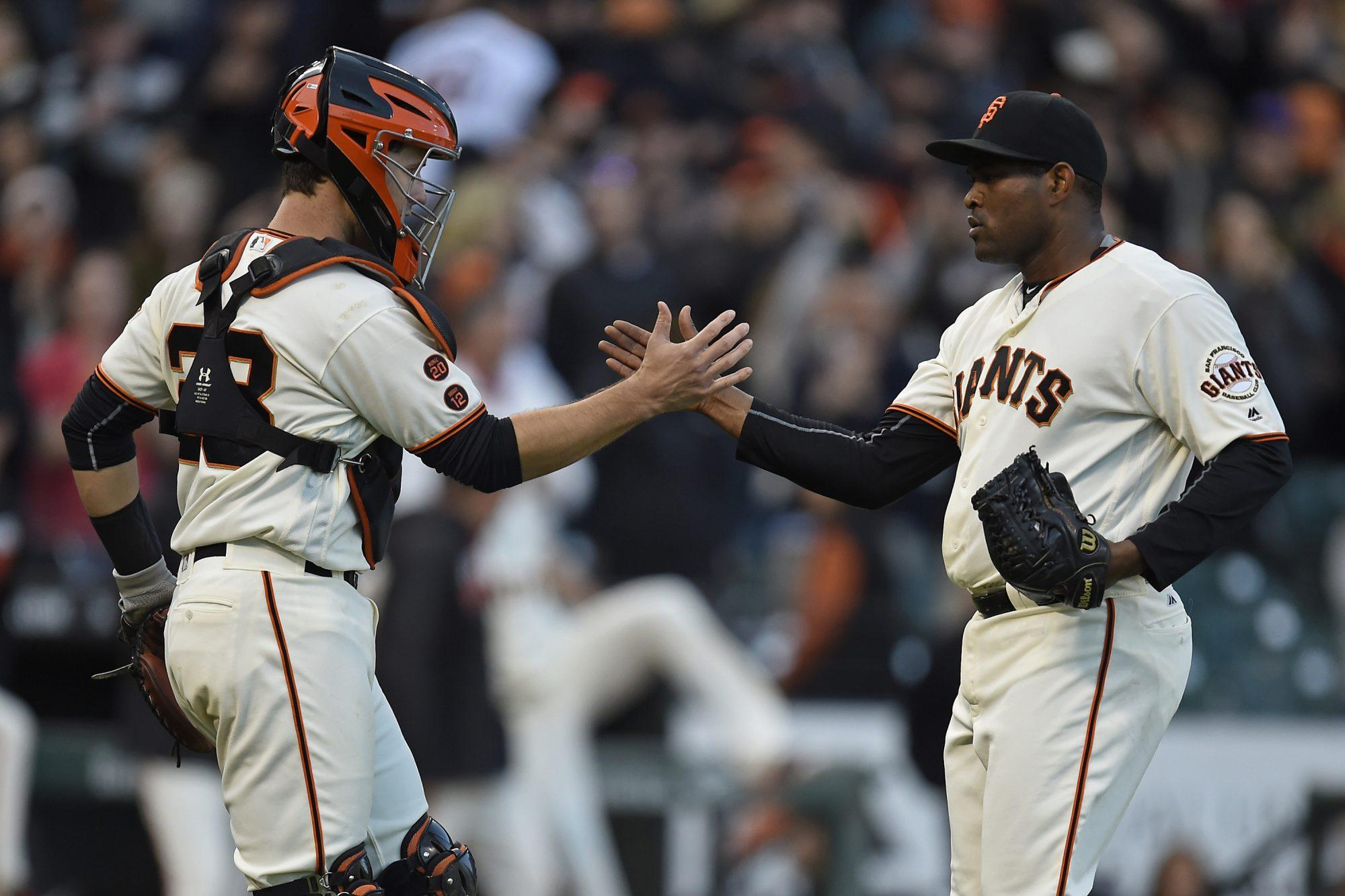 San Francisco Giants' Buster Posey (28) congratulates San Francisco Giants pitcher Santiago Casilla (46) after striking out Chicago Cubs' Addison Russell (27) to end the game on Sunday, May 22, 2016, at AT&T Park in San Francisco. (Jose Carlos Fajardo/Bay Area News Group/TNS)