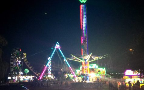View of the lit-up Ferris Wheel, The Zipper, and various other rides at the Fall Fest (P. Moore)