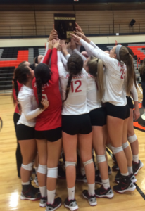 Huntley volleyball hoists their plaque after winning the regional championship in three sets (E. Kubelka).