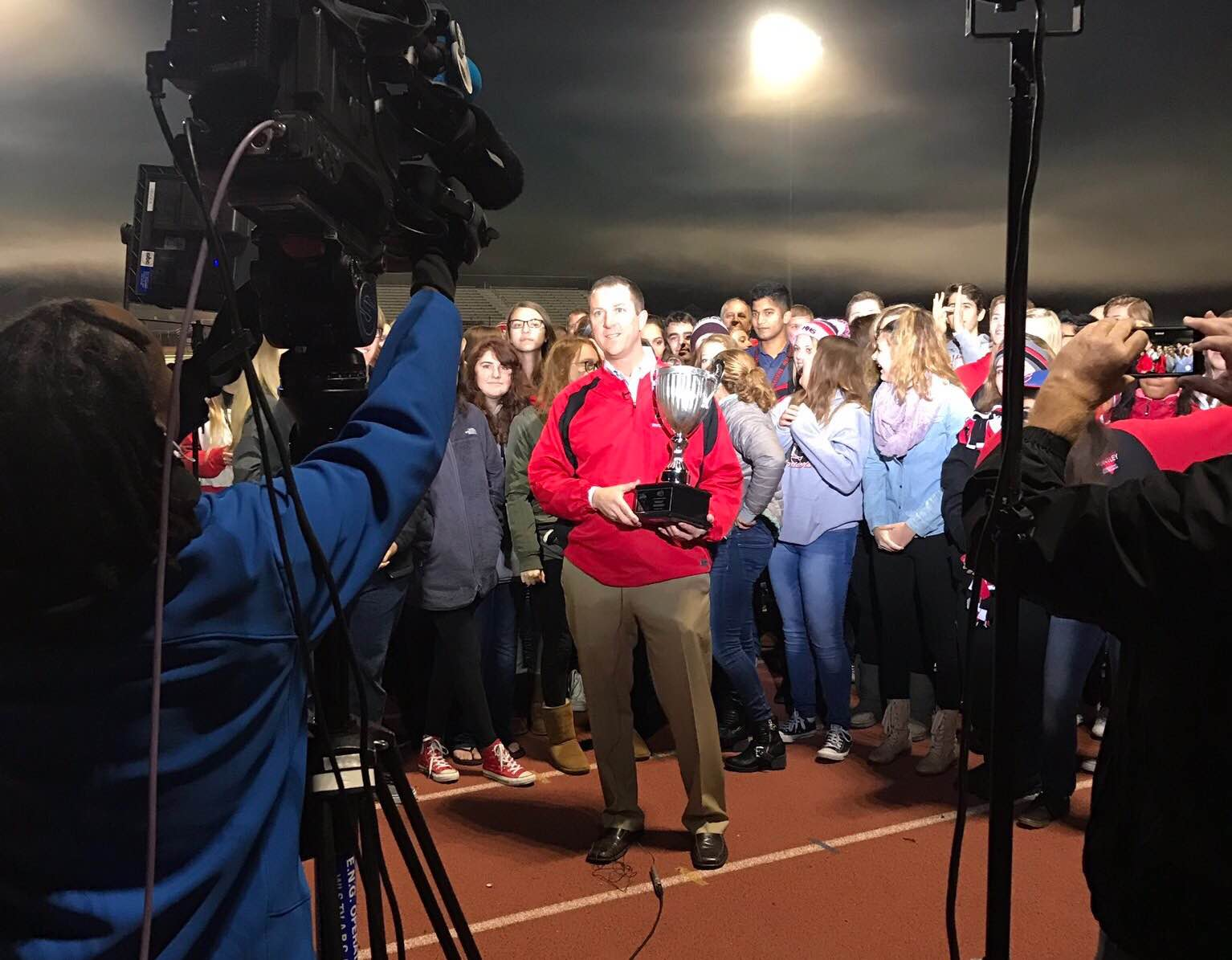 Principal Scott Rowe holds the trophy while live on ABC 7 Chicago (Courtesy of HHS Athletics twitter)