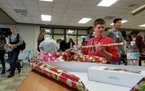Students wrap presents for the Adopt-a-Family wrapping day in the commons. (S. Faheem)