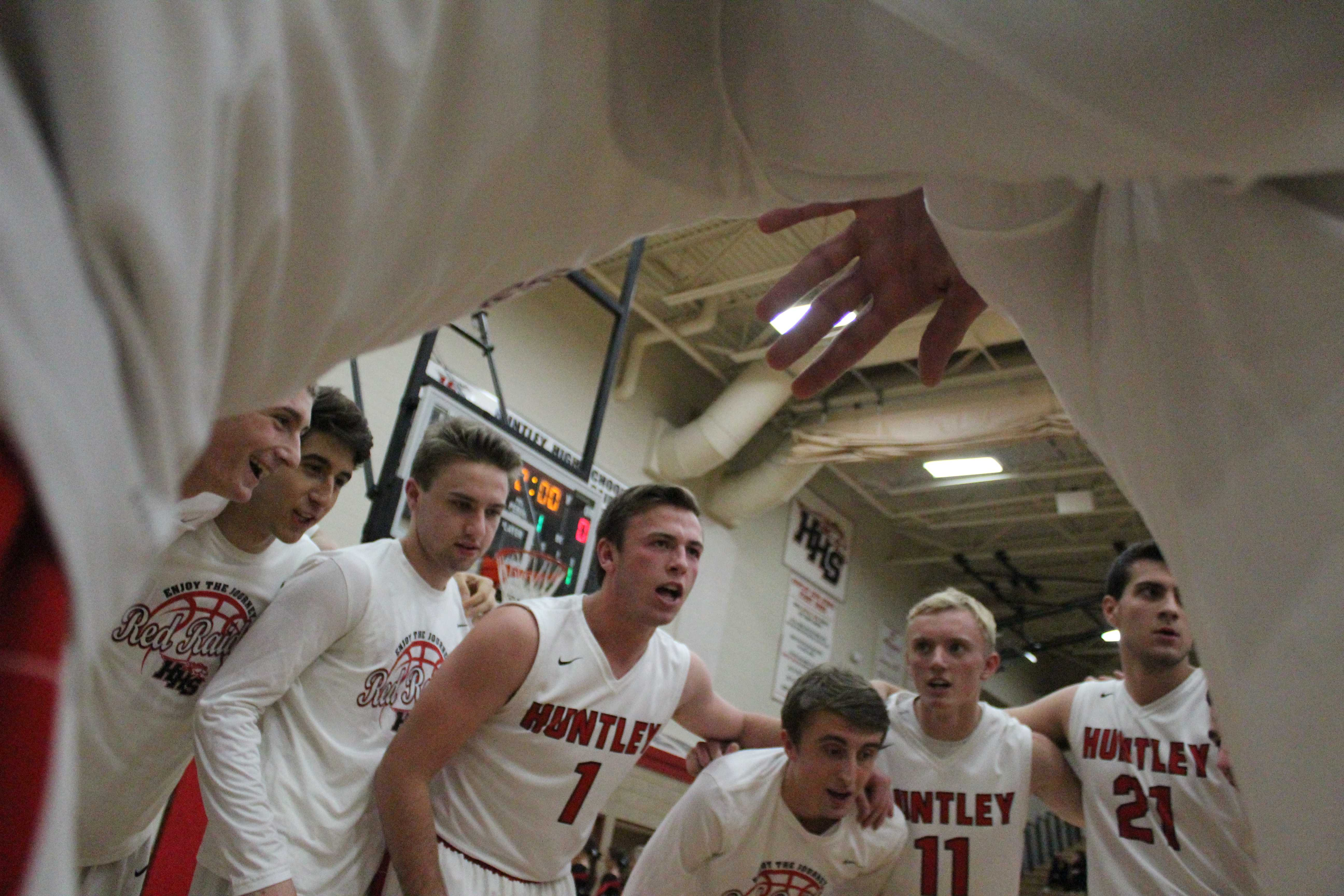 The boys varsity basketball team get in a group huddle during a game. (E. Pilat)