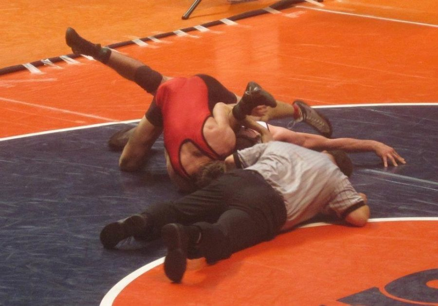 The refferre lays on the ground along with senior Josh Symbal and his opponent during state finals at the University of Illinois, Urbana-Champaign. (K.Summerville).