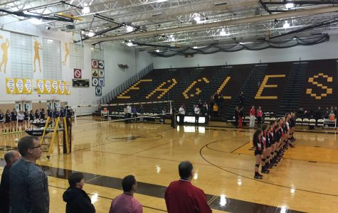 The Huntley Red Raiders varsity volleyball team stands for the national anthem before their regional championship.