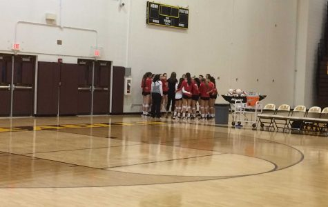 Huntley High School's varsity volleyball team huddles together during a time out to talk strategy for the remainder of the game (C. Thomas).