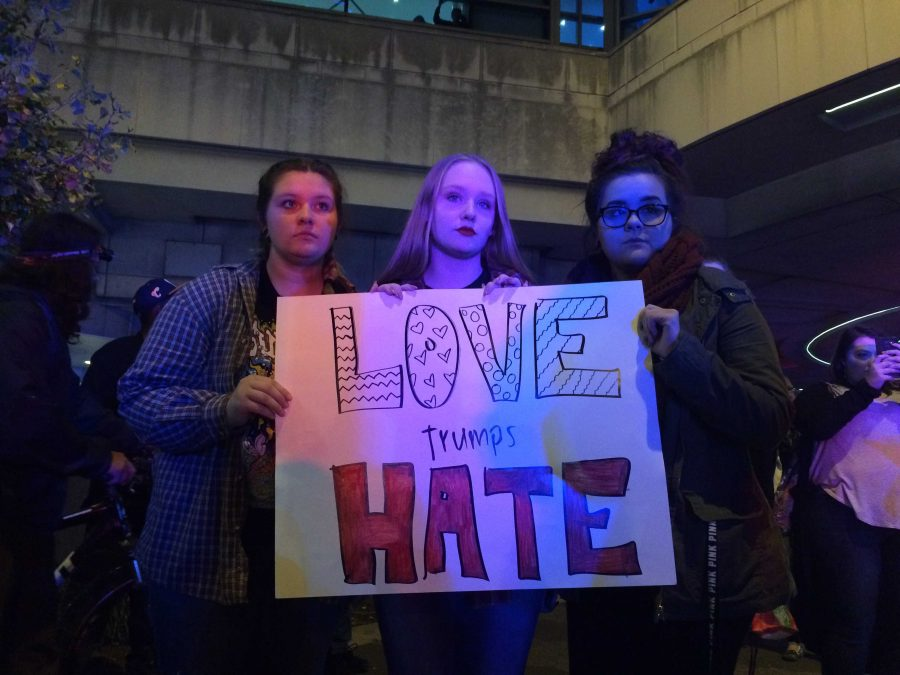 Protesters+at+the+Trump+Rally+holding+up+their+homemade+sign.+%28Photo+courtesy+of+E.+Pilat%29
