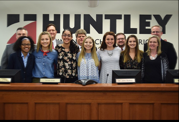 Huntley High School students stand with District 158 board members after the meeting (Courtesy of @dist158).