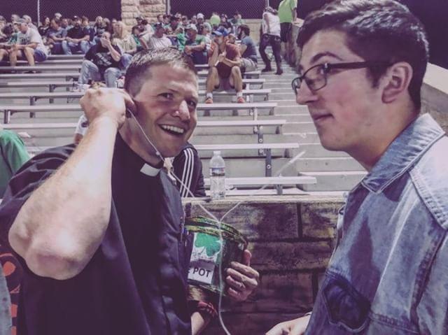 Stevenson having a priest listen to music he likes. (Photo courtesy of C. Stevenson.)