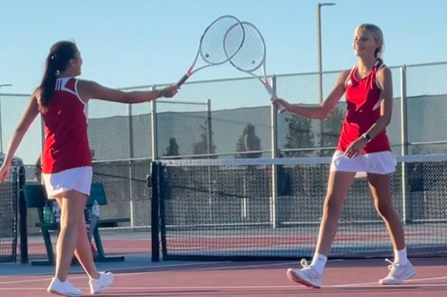 Freshman Kate Burkey and junior Emily Chong celebrate with a racket tap after scoring a particularly difficult point against Dundee-Crown. (A. Wiley)