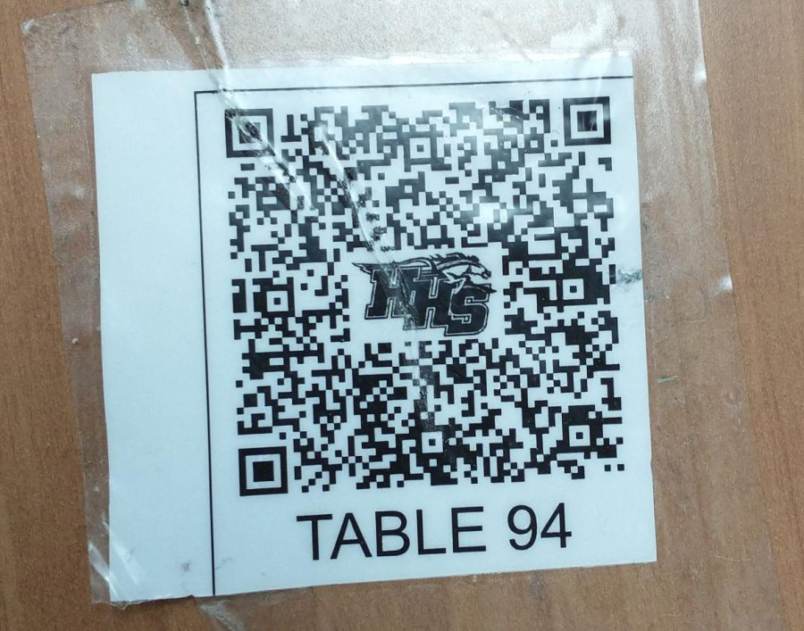 Students scan the QR codes taped to every lunch table, which is linked to a google form for contact tracing. (A.Peters)