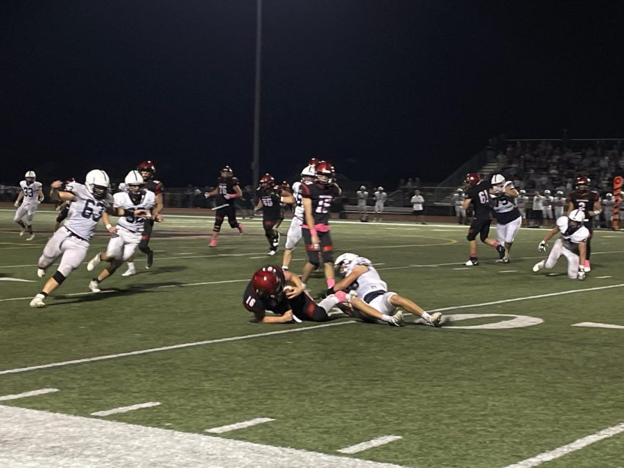 Ryder Hunkins holds on tight to the ball, despite being tackled. (Courtesy of Callen Hogberg)